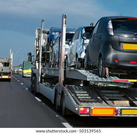 The trailer transports cars on the highway