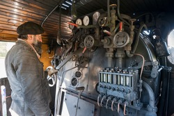 The train driver near the steam locomotive boiler keeps an eye on the vapor pressure