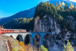 The train of  Rhaetian Railway running on the famous Landwasser Viaduct into the tunnel, on a sunny autumn day, Canton of Grisons, Switzerland