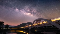 The train on a river bridge at night. Stars and the Milky Way in the beautiful sky