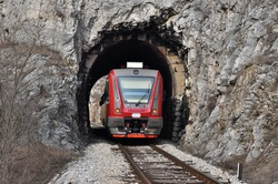 The train on the railway line comes from a small tunnel. New train on old railway.