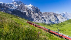 The train to Jungfraujoch departs on a clear blue day cutting through the picturesque Swiss Alpine landscape