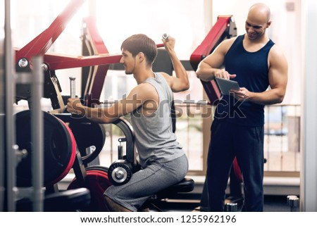 The trainer controls the physical exercise of the man on the training apparatus. Individual training with a trainer at the training apparatus. Physical exercise on the strength of the muscles the arms