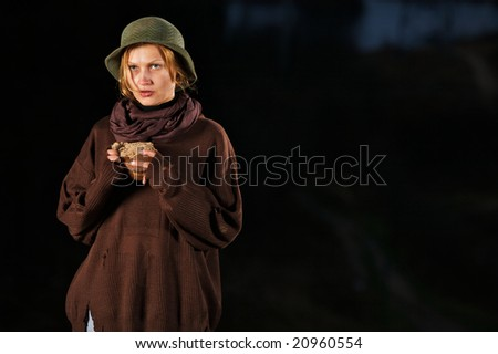 The tramp young woman at night. In hands bread. Place for text.