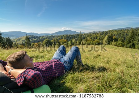 The travel photographer is resting on a clearing in the forest and looking at the mountains
