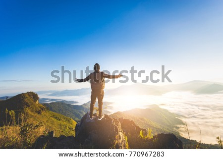The traveler travel man standing on the top of the hill and enjoy the beautiful scenery, the concept of freedom.