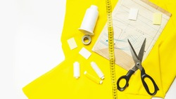 The trendy color of 2021. Tailoring concept. Accessories for sewing and needlework. measuring tape, chalk, thread and yellow fabric and pattern on white background. Top view. copy space