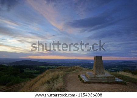 The trigonometrical point at twilight  looking towards Gloucester and the Malvern hills from Painswick Beacon, The Cotswolds, Gloucestershire, United Kingdom