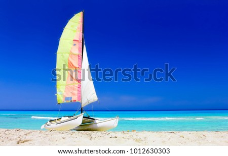 The tropical beach of Varadero in Cuba with a colorful sailboat catamaran on a summer day with turquoise water #1012630303