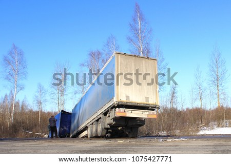 The truck in the ditch – crash, skid, black ice, accidents in the winter on the background of the road, trees and blue clear sky. The driver is talking on the phone. #1075427771