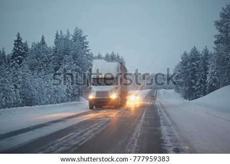 The truck rides on a winter snowy road in the forest. Dangerous driving conditions in winter in cloudy weather. #777959383