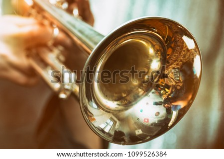 The trumpeter is playing on a silver trumpet. Trumpet player