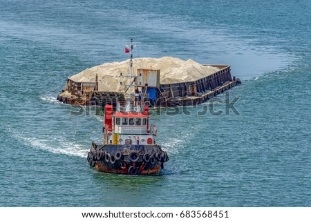 The tug boat towing a barge with sand in coastal waterway near Singapore