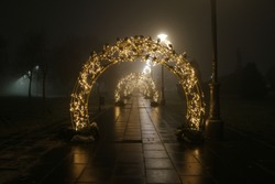 The tunnel of light, New Year and Christmas lighting decoration in the fogg at night, January 2020.