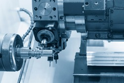 The turn-mill machine cutting the metal shaft part. The hi-precision manufacturing process by multi-tasking CNC lathe machine.