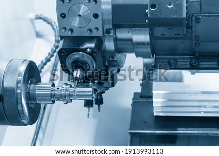 The turn-mill machine cutting the metal shaft part. The hi-precision manufacturing process by multi-tasking CNC lathe machine. Photo stock ©