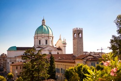 The turquoise dome with stone white sculptures of the central catholic church (Cathedral) (Duomo Vecchio) of Brescia and Clock tower, Lombardy, Italy. Close up. Panoramic view. A sunny summer day.