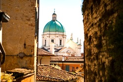 The turquoise dome with stone white sculptures of the central duomo of Brescia, Lombardy, Italy. Close up view from the narrow street through Italian houses on a sunny summer day. Italian architecture