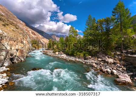 The turquoise river in mountains under the cloudy sky. #318507317