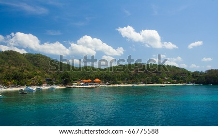 The turquoise water and white sand beach of the port village of Padang Bai, home of the island hopping ferry to Lombok in Bali, Indonesia seen from a boat