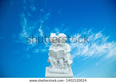 The twin baby statue  and blue sky,The boy statue is sitting reading a book,Twin statue of a female girl and a boy.