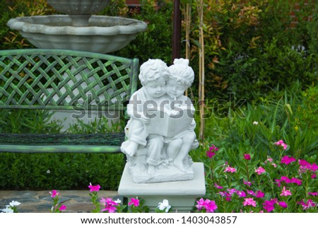 The twin baby statue,The boy statue is sitting reading a book,Twin statue of a female girl and a boy in the garden.