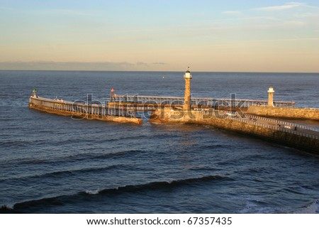The twin jetties guarding Whitby harbour at the mouth of the river Esk. - stock photo