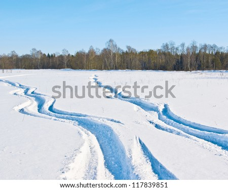 The twisting traces of a snowmobile crossing a snow-covered field under the blue sky