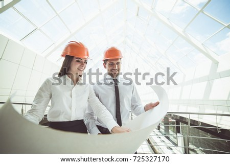 The two engineers hold the project plan in the building #725327170