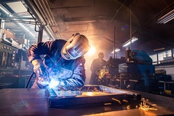 The two handymen performing welding and grinding at their workplace in the workshop, while the sparks