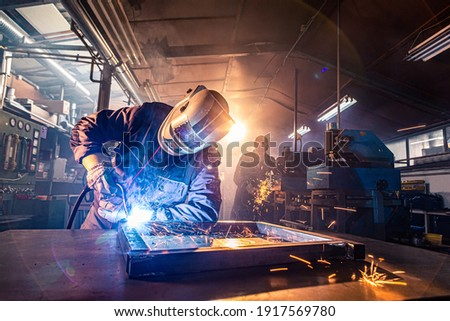 The two handymen performing welding and grinding at their workplace in the workshop, while the sparks 'fly' all around them, they wear a protective helmet and equipment. Foto stock ©