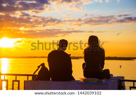 Photo of  The two lovers looked out at the water during sunset. The concept of travel. Happy couple of lovers relaxing on the sea pier under sunset sun light at evening time.