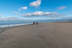 The two riders riding along the coast of the East Frisian Island Norderney, Germany