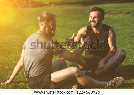 The two sportsmen handshaking on the grass on the sunny background