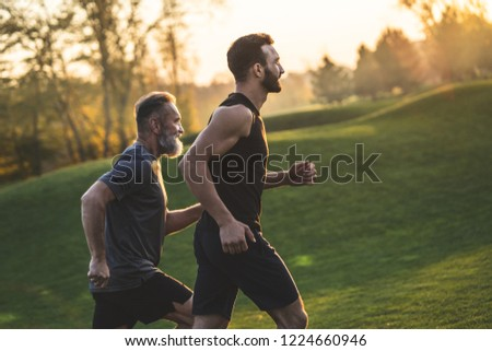 The two sportsmen running on the grass