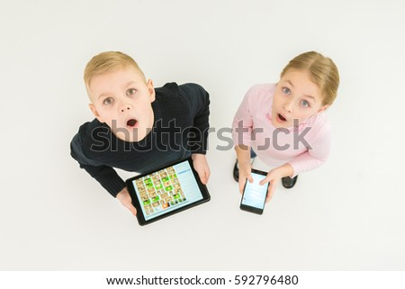 The two surprised kids stand with devices. View from above #592796480