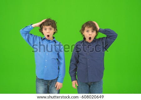 The two surprised twin kids gesture on the green background