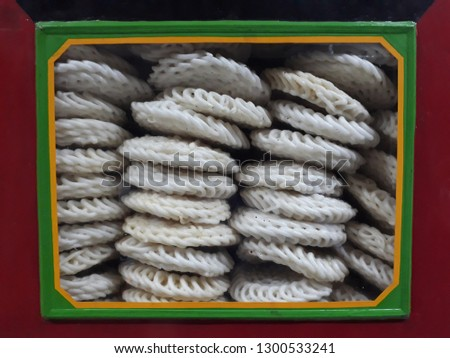 The typical container of crackers is a large red can with glass on the front. The shape is round with curly threads and large size. It feels savory and crunchy and cheap