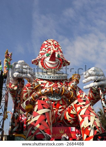 the typical mask of Viareggio carnival represented here in a cart and some masked people