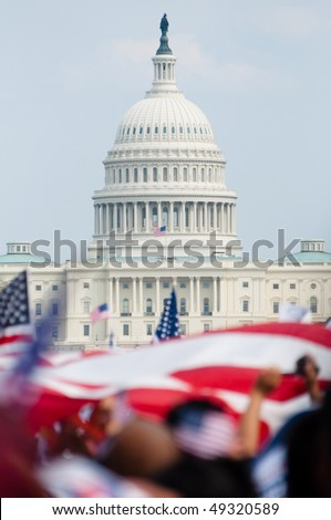 The U.S. Capitol building in the distance, American flags fly on the National Mall during a political rally.