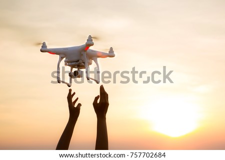 The UAV drone and photographer man hands.drone copter flying with digital camera. UAV Drone with digital camera. Flying camera take a photo and video.The drone with camera takes pictures of the sky.
