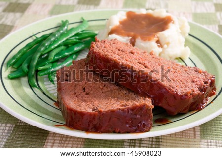 The ultimate comfort food - meat loaf prepared with ground beef, grated carrots, bread crumbs, and herbs and spices. Served with fresh green beans, mashed potatoes, and gravy.