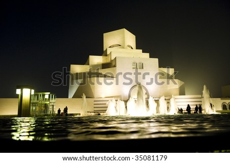 The ultra-modern Museum of Islamic Art in Doha, Qatar, across a fountain at night-time.