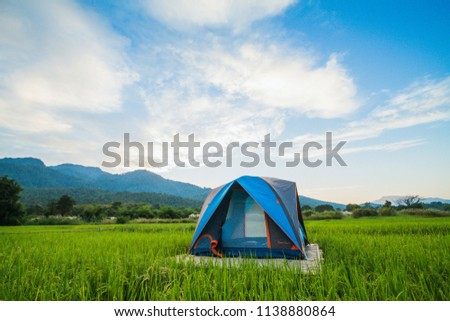 The umbrella tents were installed on rice paddies for tourists to stay in tents to help with rain and breeze at night for a comfortable stay in nature. Travel and camping in the meadow with a tent. #1138880864