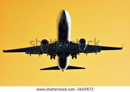 The underview of a large commercial jet with yellow golden backdrop.