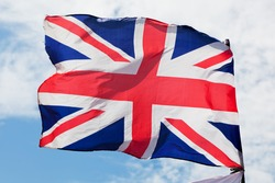 The Union Jack, the national flag of the United Kingdom waving on wind against blue sky