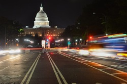 The United States Capitol building at night as seen from Pennsylvania Avenue with car lights trails - Washington DC, United States