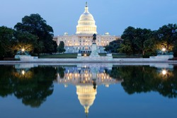 The United States Capitol building in Washington DC, USA - after dark with water reflection