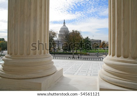 The United States Capitol building viewed from the marble columns of the Supreme Court.