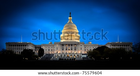 The United States Capitol building with the dome lit up at night.  Both the Senate and House sides of the building are fully shown. - Shutterstock ID 75579604